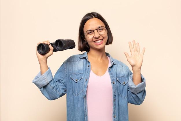 Jonge latijnse vrouw die vrolijk en opgewekt lacht, met de hand zwaait en je groet, of afscheid neemt
