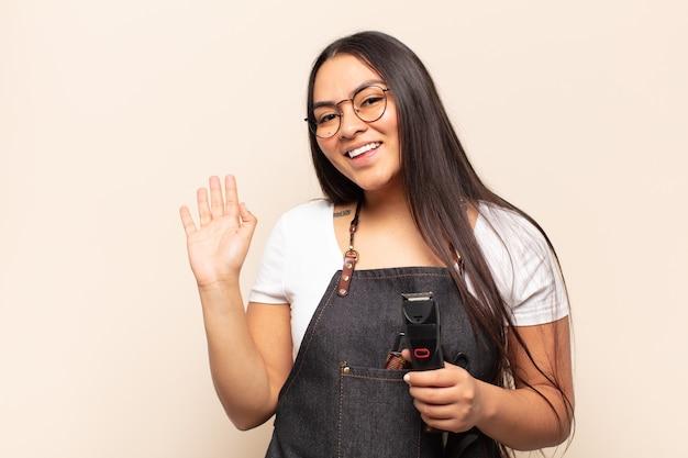 Jonge latijnse vrouw die vrolijk en opgewekt lacht, met de hand zwaait, je verwelkomt en begroet, of afscheid neemt