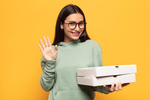 Jonge latijnse vrouw die vrolijk en vrolijk lacht, met de hand zwaait, je verwelkomt en begroet