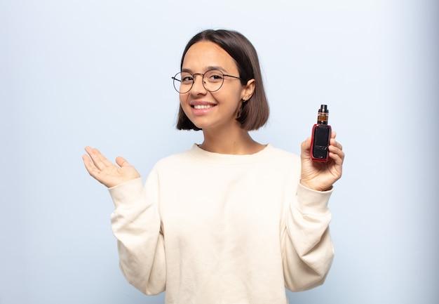 Jonge latijnse vrouw die vrolijk glimlacht, zich gelukkig voelt en een concept in exemplaarruimte met handpalm toont