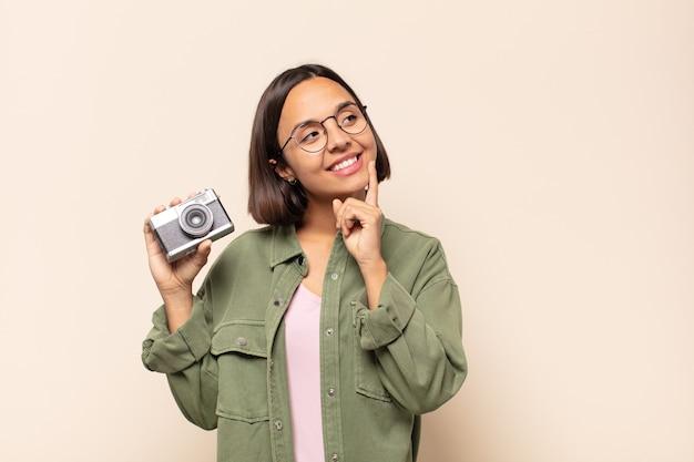 Jonge latijnse vrouw die vrolijk lacht en dagdroomt of twijfelt, opzij kijkend
