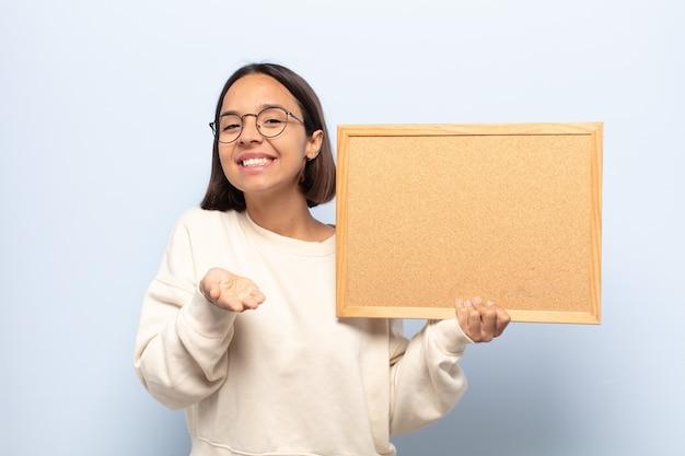 Jonge latijnse vrouw die vrolijk lacht met een vriendelijke, zelfverzekerde, positieve blik, een object of concept aanbiedt en toont