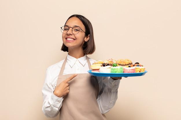 Jonge latijnse vrouw die vrolijk lacht, zich gelukkig voelt en naar de zijkant en naar boven wijst, een object in de kopieerruimte laat zien Premium Foto
