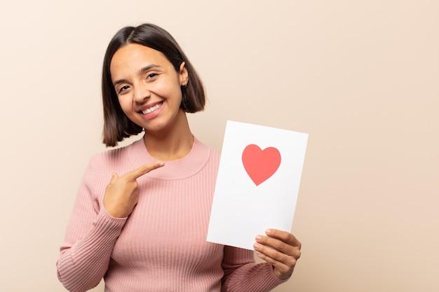 Jonge latijnse vrouw die vrolijk lacht, zich gelukkig voelt en naar de zijkant en naar boven wijst, een object in de kopieerruimte laat zien