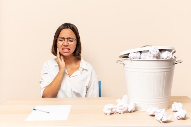 Jonge latijnse vrouw die wang vasthoudt en pijnlijke kiespijn heeft, zich ziek, ellendig en ongelukkig voelt, op zoek naar een tandarts