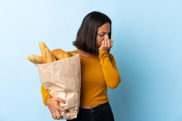 Jonge latijnse vrouw die wat brood koopt