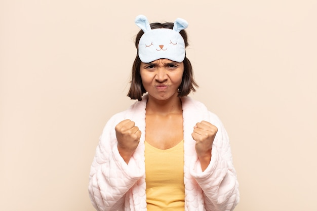 Jonge latijnse vrouw die zelfverzekerd, boos, sterk en agressief kijkt, met vuisten klaar om te vechten in bokspositie