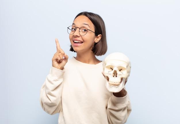 Jonge latijnse vrouw die zich als een gelukkig en opgewonden genie voelt na het realiseren van een idee, vrolijk vinger opstekend, eureka!