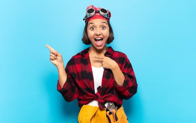 Jonge latijnse vrouw die zich blij en verrast voelt, lacht met een geschokte uitdrukking en naar de zijkant wijst