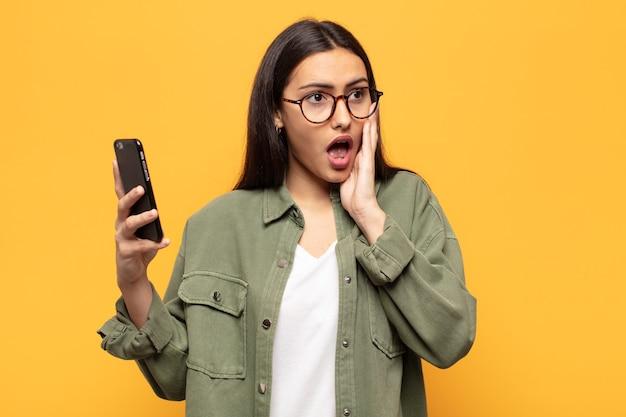 Jonge latijnse vrouw die zich blij, opgewonden en verrast voelt, opzij kijkt met beide handen op het gezicht