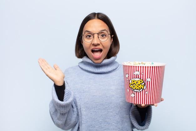 Jonge latijnse vrouw die zich blij, opgewonden, verrast of geschokt voelt, lacht en verbaasd is over iets ongelooflijks