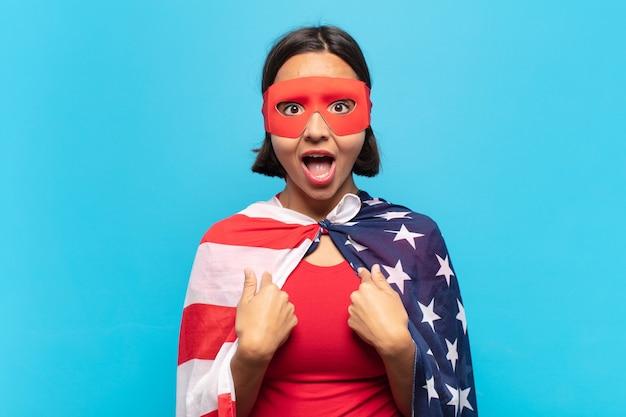 Jonge latijnse vrouw die zich blij, verrast en trots voelt en naar zichzelf wijst met een opgewonden, verbaasde blik