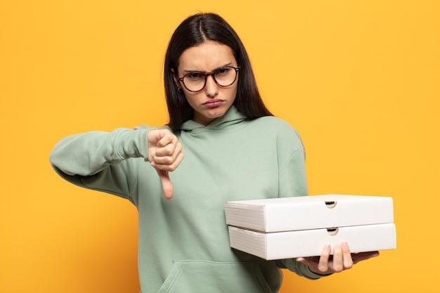 Jonge latijnse vrouw die zich boos, boos, geïrriteerd, teleurgesteld of ontevreden voelt, duimen naar beneden toont met een serieuze blik