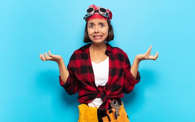 Jonge latijnse vrouw die zich geen idee en verward voelt, niet zeker welke keuze of optie ze moet kiezen, zich afvragend?