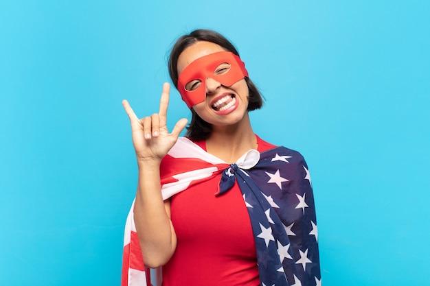 Jonge latijnse vrouw die zich gelukkig, leuk, zelfverzekerd, positief en rebels voelt en rock of heavy metal met de hand tekent