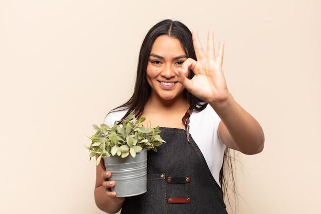 Jonge latijnse vrouw die zich gelukkig, ontspannen en tevreden voelt en goedkeuring toont met een goed gebaar