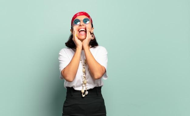Jonge latijnse vrouw die zich gelukkig, opgewonden en positief voelt, een grote schreeuw geeft met de handen naast de mond, roept,
