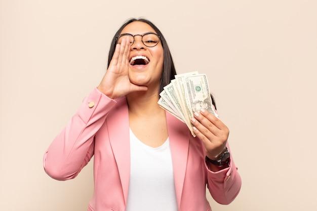 Jonge latijnse vrouw die zich gelukkig, opgewonden en positief voelt, een grote schreeuw geeft met handen naast de mond, roept