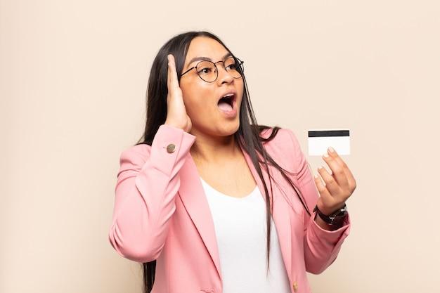 Jonge latijnse vrouw die zich gelukkig, opgewonden en verrast voelt, opzij kijkend met beide handen op het gezicht