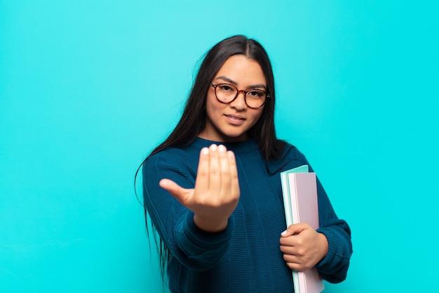 Jonge latijnse vrouw die zich gelukkig, succesvol en zelfverzekerd voelt, een uitdaging aangaat en zegt: kom maar op! of je verwelkomen