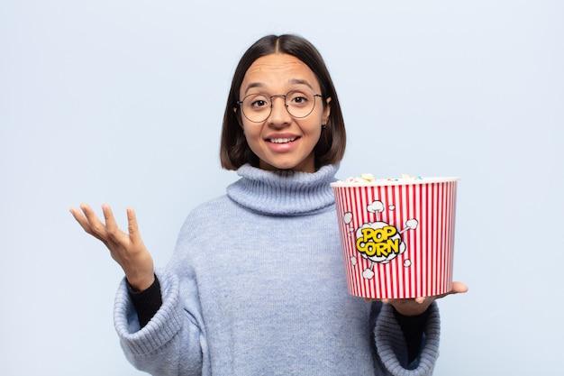 Jonge latijnse vrouw die zich gelukkig, verrast en opgewekt voelt, glimlachend met een positieve houding, een oplossing of idee realiserend