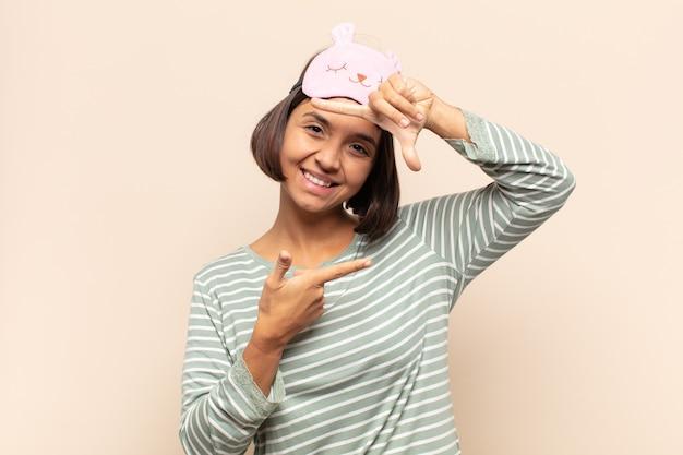 Jonge latijnse vrouw die zich gelukkig, vriendelijk en positief voelt, lacht en een portret of fotolijst maakt met handen