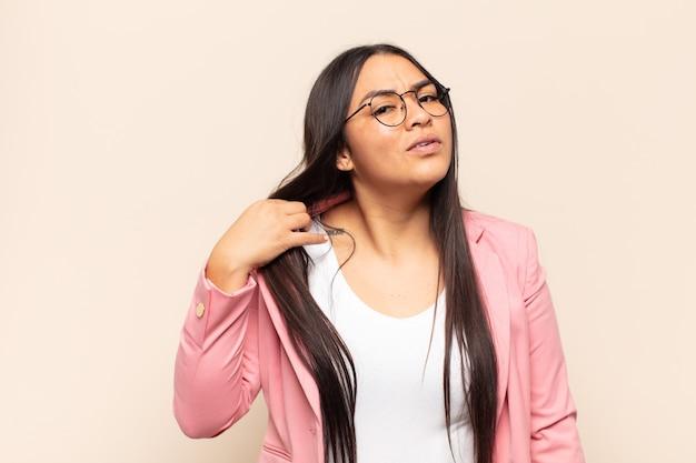 Jonge latijnse vrouw die zich gestrest, angstig, moe en gefrustreerd voelt, aan de hals van het shirt trekt, gefrustreerd kijkt door het probleem