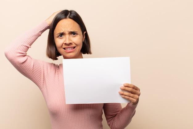 Jonge latijnse vrouw die zich gestrest, bezorgd, angstig of bang voelt, met de handen op het hoofd, in paniek bij vergissing