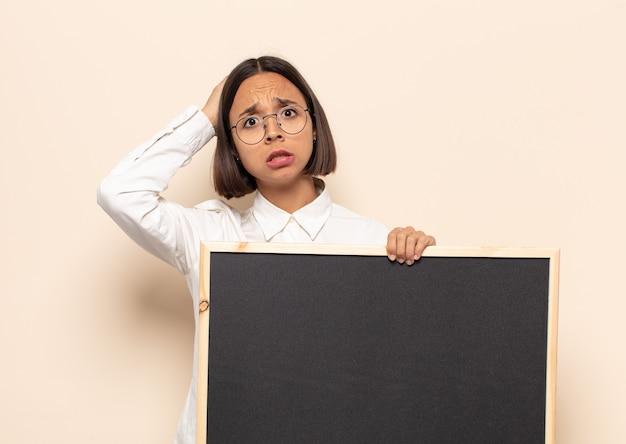 Jonge latijnse vrouw die zich gestrest, bezorgd, angstig of bang voelt, met de handen op het hoofd, in paniek raakt bij een vergissing