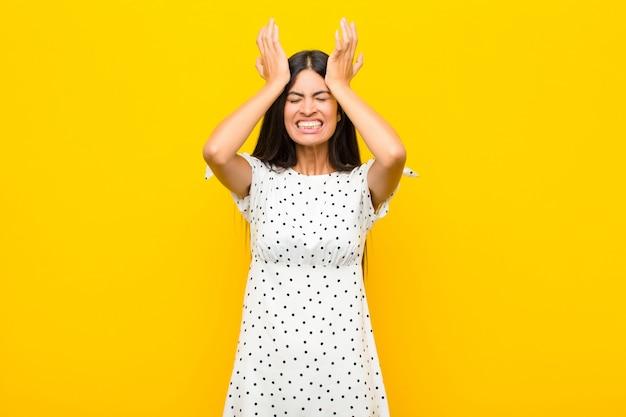 Jonge latijnse vrouw die zich gestrest en angstig, depressief en gefrustreerd voelt door hoofdpijn, beide handen opheft naar het hoofd op een vlakke muur