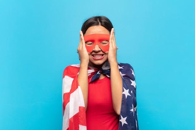 Jonge latijnse vrouw die zich gestrest en angstig, depressief en gefrustreerd voelt door hoofdpijn, beide handen opheft naar het hoofd