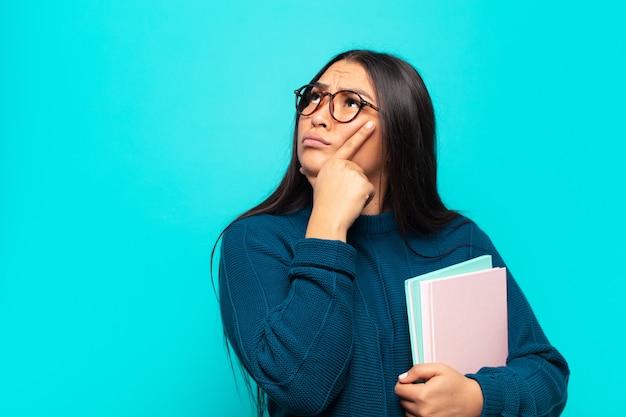 Jonge latijnse vrouw die zich nadenkend voelt, zich afvraagt of zich ideeën voorstelt, dagdroomt en omhoog kijkt om ruimte te kopiëren