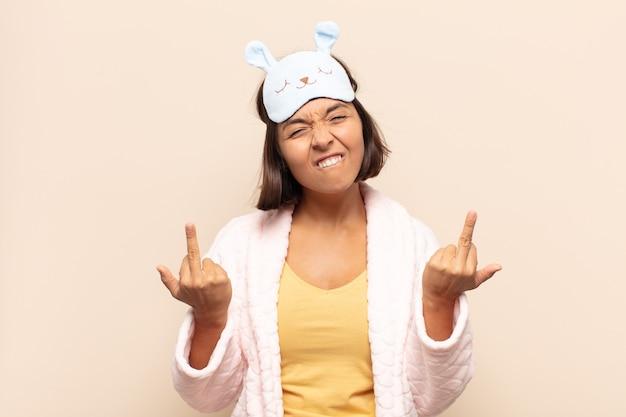 Jonge latijnse vrouw die zich provocerend, agressief en obsceen voelt, de middelvinger wegknipt, met een rebelse houding