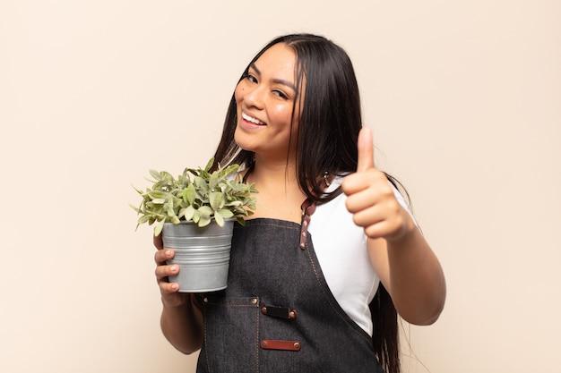 Jonge latijnse vrouw die zich trots, zorgeloos, zelfverzekerd en gelukkig voelt, positief glimlacht met omhoog duimen