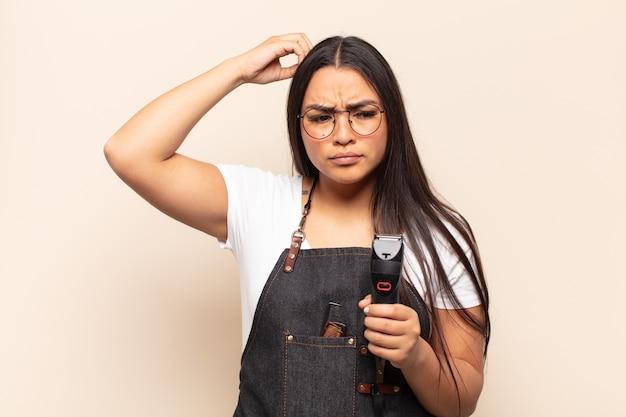 Jonge latijnse vrouw die zich verbaasd en verward voelt, haar hoofd krabt en naar de zijkant kijkt