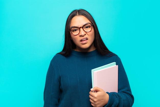 Jonge latijnse vrouw die zich verbaasd en verward voelt, met een domme, verbijsterde uitdrukking op zoek naar iets onverwachts