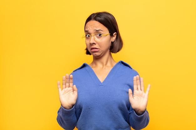 Jonge latijnse vrouw die zich verdoofd en bang voelt, bang voor iets angstaanjagends, met de handen open vooraan en zegt blijf weg