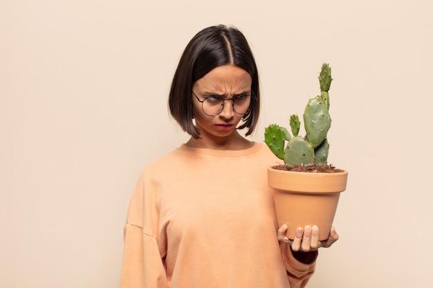 Jonge latijnse vrouw die zich verdrietig, boos of boos voelt en naar de zijkant kijkt met een negatieve houding, fronst van onenigheid