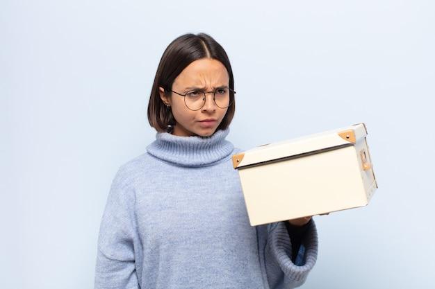 Jonge latijnse vrouw die zich verdrietig, overstuur of boos voelt en opzij kijkt met een negatieve houding, fronsend in onenigheid