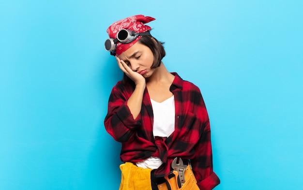 Jonge latijnse vrouw die zich verveeld, gefrustreerd en slaperig voelt na een vermoeiende, saaie en vervelende taak, gezicht met hand vasthoudend