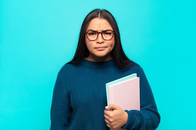 Jonge latijnse vrouw die zich verward en twijfelachtig voelt, zich afvraagt of probeert te kiezen of een beslissing te nemen