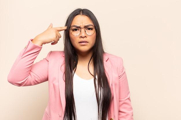 Jonge latijnse vrouw die zich verward en verbaasd voelt en laat zien dat je gek, gek of gek bent