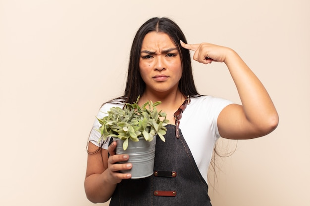 Jonge latijnse vrouw die zich verward en verbaasd voelt, laat zien dat je gek, gek of gek bent