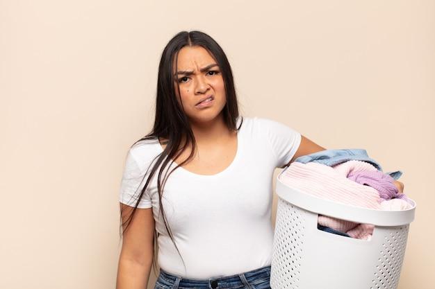 Jonge latijnse vrouw die zich verward en verward voelt, met een stomme, verbijsterde uitdrukking op zoek naar iets onverwachts