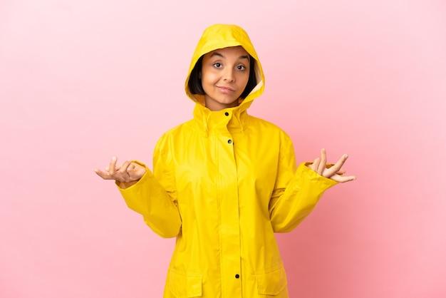Jonge latijnse vrouw draagt een regenbestendige jas over geïsoleerde achtergrond gelukkig en glimlachend