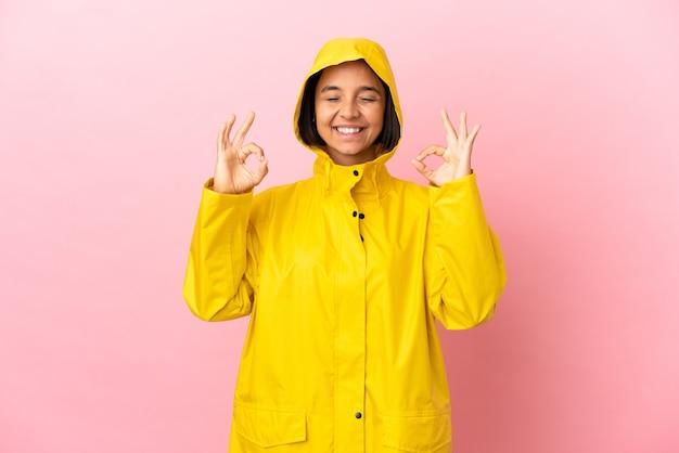 Jonge latijnse vrouw draagt een regenbestendige jas over geïsoleerde achtergrond in zen posezen