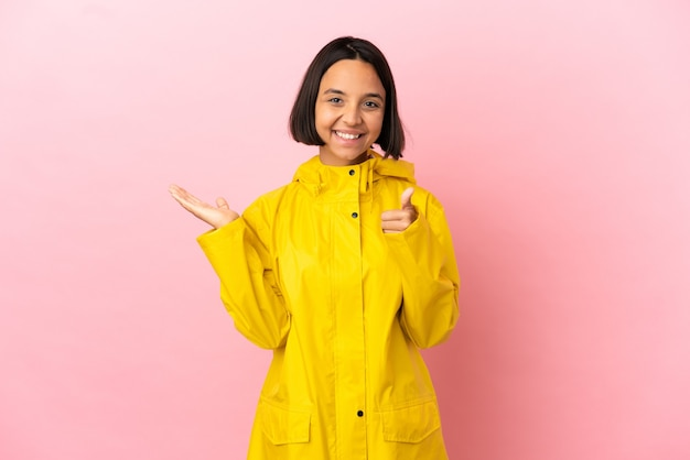 Jonge latijnse vrouw draagt een regenbestendige jas over geïsoleerde achtergrond met copyspace denkbeeldig op de palm om een advertentie in te voegen en met duimen omhoog