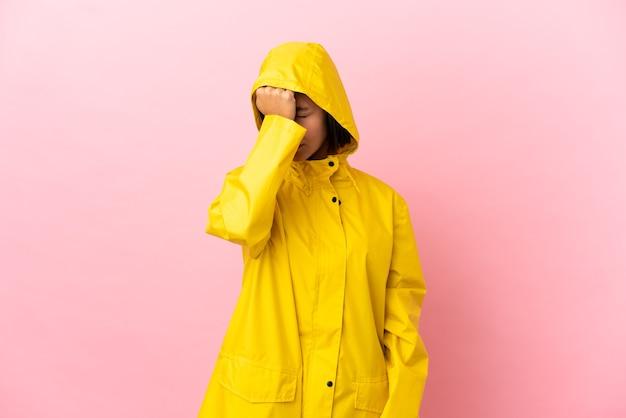 Jonge latijnse vrouw draagt een regenbestendige jas over geïsoleerde achtergrond met hoofdpijn with