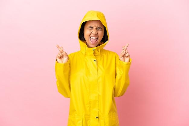 Jonge latijnse vrouw draagt een regenbestendige jas over geïsoleerde achtergrond met vingers over elkaar