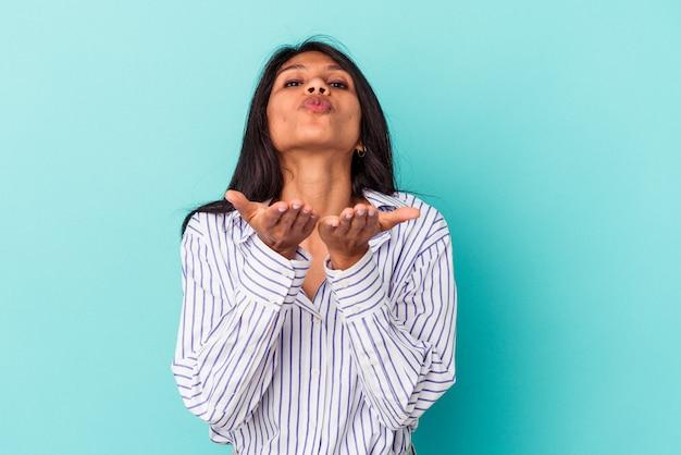 Jonge latijnse vrouw geïsoleerd op blauwe achtergrond die lippen vouwt en handpalmen vasthoudt om luchtkus te sturen.